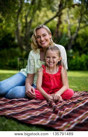 Portrait of smiling mother and daughter sitting on blanket in yard