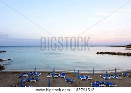 Photo of beach and sea in protaras cyprus island with beach chairs and rocks at sunset.