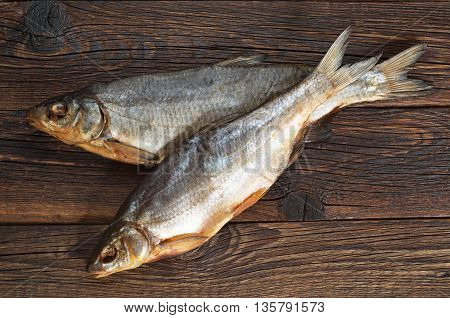 Salty dry fishes for beer on a wooden background top view