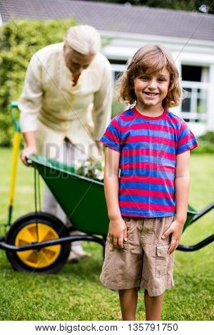 Boy smiling while standing against grandmother with wheelbarrow in yard