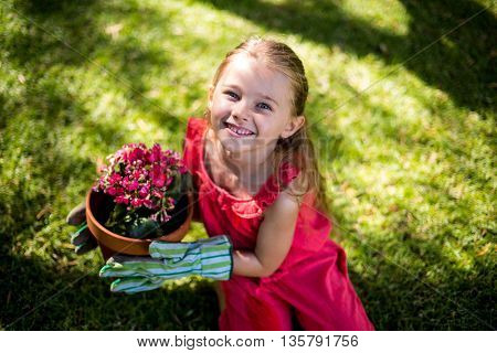 High angle portrait of smiling girl holding flower pot in yard