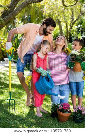 Smiling parents with children gardening in yard