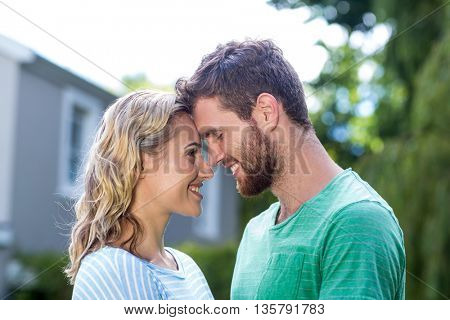 Smiling couple touching head in yard