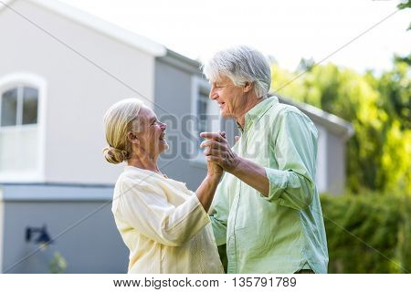 Senior couple dancing in yard against house