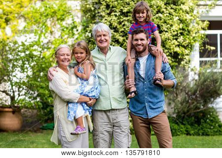 Portrait of grandparents with grandchildren and son at yard
