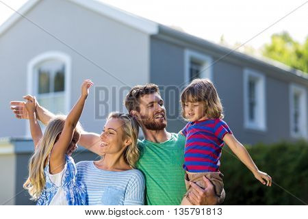 Parents carrying children with arms raised standing against house