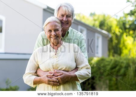 Portrait of senior couple embracing against house
