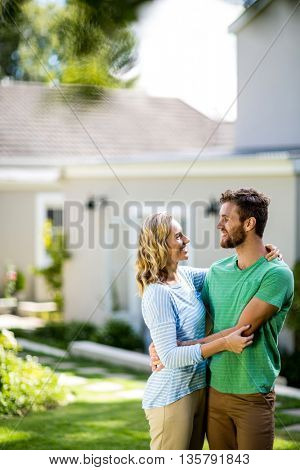 Smiling couple hugging in yard against house