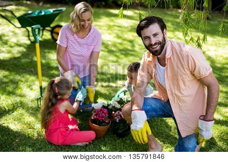 Smiling father against family during gardening in yard