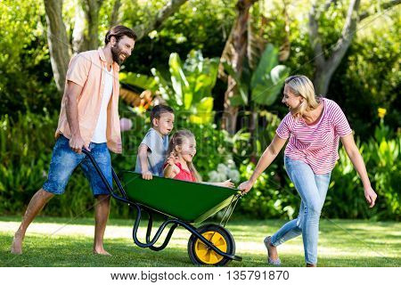 Happy parents pushing children sitting in wheelbarrow at yard