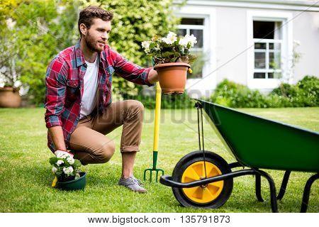 Full length of gardener holding potted plants in yard
