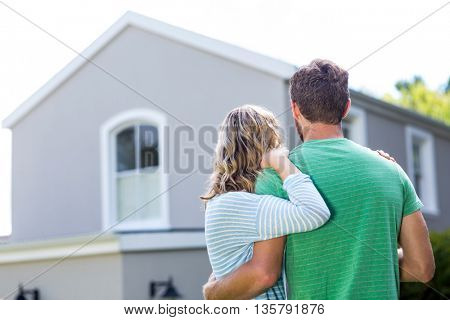 Rear view of couple standing against house