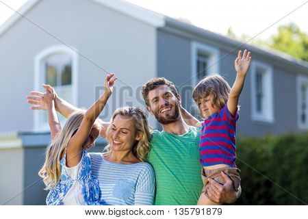 Happy parents carrying children with arms raised standing against house
