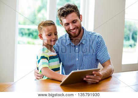 Smiling father and son looking into digital tablet at home