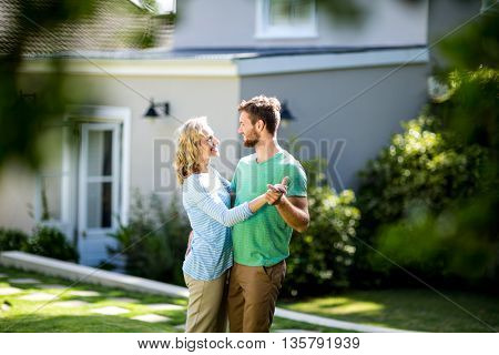 Smiling couple dancing in yard against house