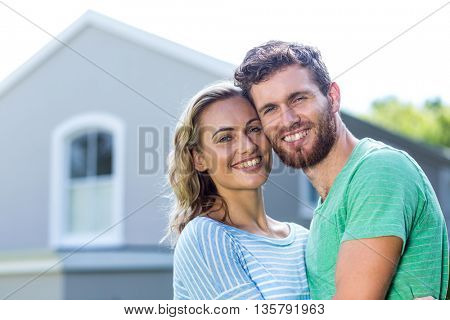 Portrait of smiling couple standing against house