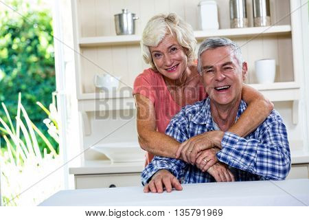 Portrait of smiling senior couple hugging in kitchen at home