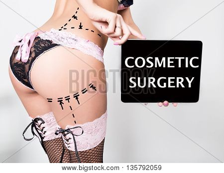 young woman in lacy lingerie, holding a tablet pc with cosmetic surgery sign. Drawing lines on a Caucasian woman's ass as marks for ass cellulite cosmetic correction surgery.