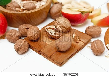 There are Apple,Walnuts in the Wooden Plate,Trivet,Healthy Fresh Organic Food on the White Background