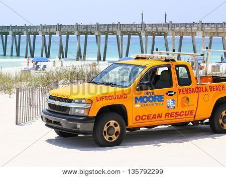 PENSACOLA BEACH, USA - MAY 13, 2015: Lifeguard pick-up truck in front of the beach and the Pensacola Beach Gulf Pier.