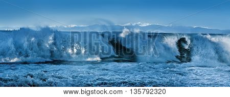 panoramic view of high stormy waves and snow-capped mountains sealine