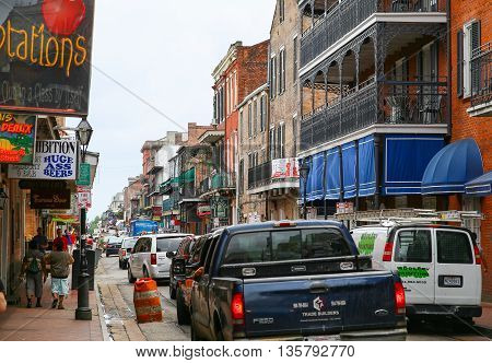 NEW ORLEANS, USA - MAY 14, 2015: Cars driving and people strolling down Bourbon Street in the French Quarter. There are colorful buildings to both sides of the street some with balconies and many with neon signs of bars.