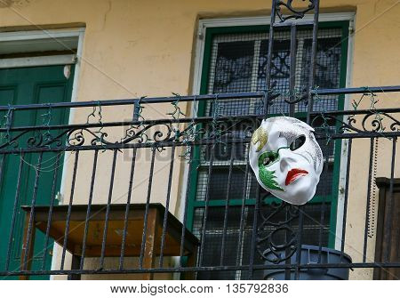 NEW ORLEANS, USA - MAY 14, 2015: A carnival mask attached to a balcony in Bourbon Street in French Quarter.