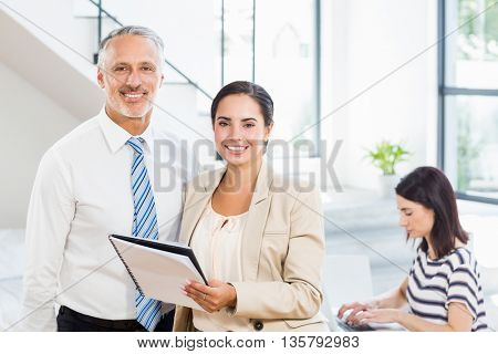 Portrait of businesspeople holding diary in the office