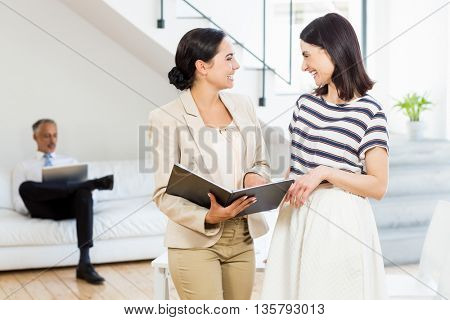 Businesswoman and a colleague interacting and holding diary in the office