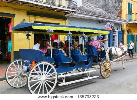 NEW ORLEANS, USA - MAY 14, 2015: Group of people in a carriage on a sightseeing tour on Bourbon Street in French Quarter.