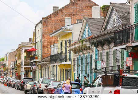NEW ORLEANS, USA - MAY 14, 2015: Colorful historic buildings on Bourbon Street in French Quarter many of them with balconies.