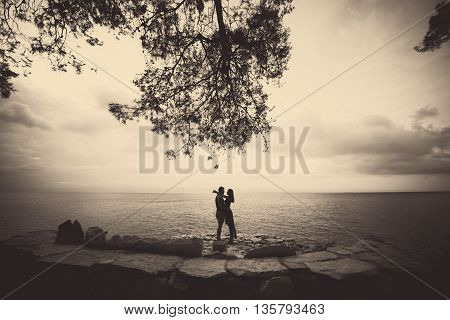 Loving couple share a romantic moment on sea side with wonderful sea view. Couple kissing after romantic engagement proposal. Young couple in love enjoying romantic evening.Date.Honeymoon