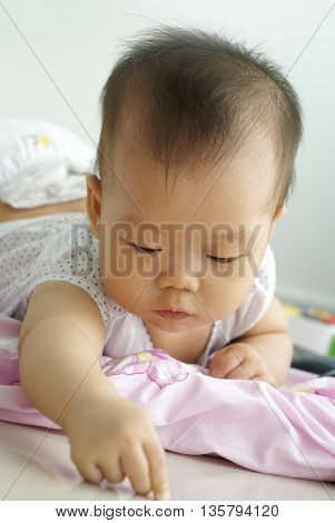 Cute Asian baby lying on the floor. Little Asian infant playing on the floor.