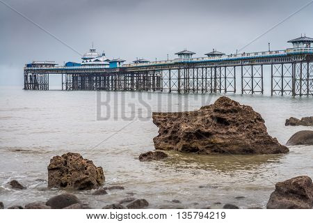 Llandudno Pier receding into the distance above rocky outcrops on the beach