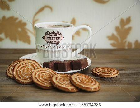 There are Cookies,Chocolate Candy, Porcelain Saucer and Cap with Coffee,Tasty Sweet Food on the Wooden Background