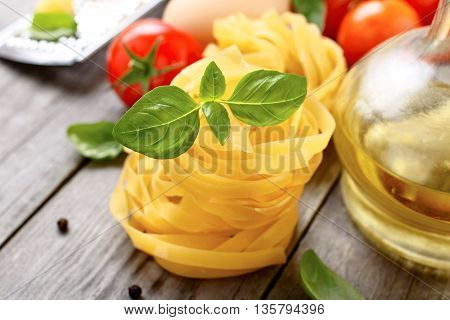 Fettuccine with basil leaves closeup on a wooden table