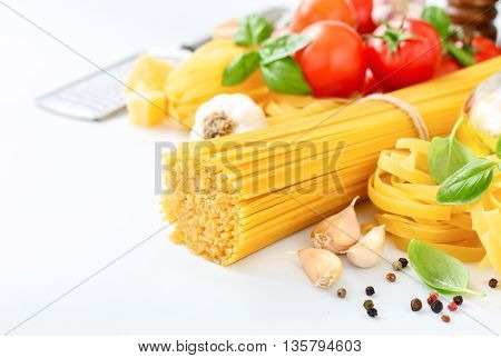 Spaghetti and fettuccine with ingredients for cooking pasta on a white background closeup