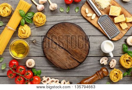 Spaghetti and fettuccine with ingredients for cooking pasta on wooden table with blank of round wooden board top view. Rustic style