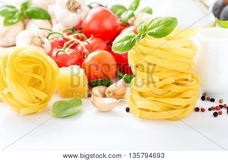 Fettuccine closeup with ingredients for cooking pasta on a white background