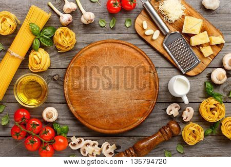 Spaghetti and fettuccine with ingredients for cooking pasta on wooden table with blank of round wooden kitchen board top view. Rustic style. Flat lay