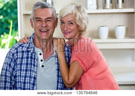 Portrait of smiling senior man with woman in kitchen at home