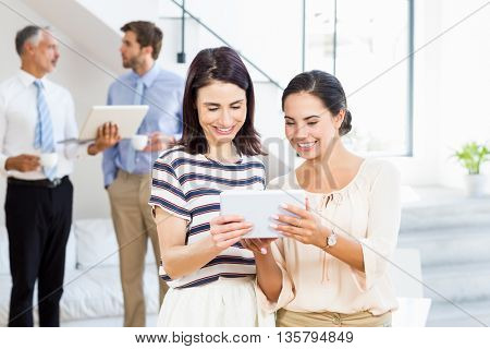 Businesswomen are looking at their notes with a background which there are workers who talking