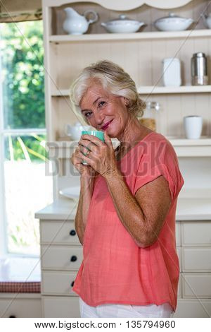 Portrait of smiling senior woman having coffee in kitchen at home