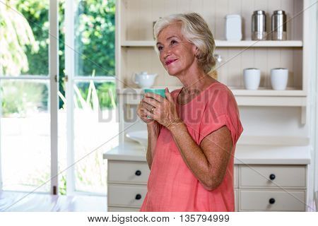 Smiling senior woman having coffee in kitchen at home