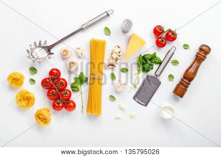 Fettuccine and spaghetti with ingredients for cooking pasta on a white background top view. Flat lay