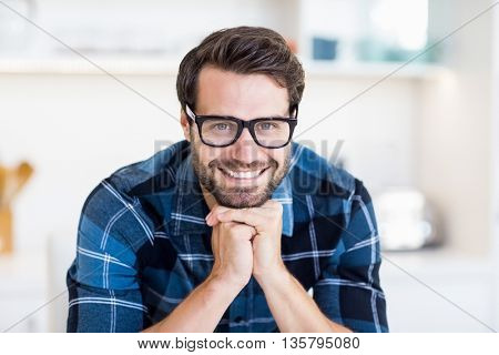 Portrait of young man in spectacles smiling at camera in the kitchen