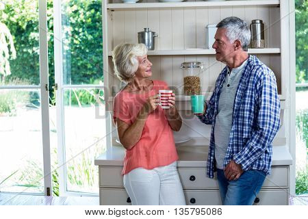 Happy senior couple having coffee in kitchen at home