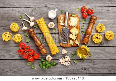 Spaghetti and fettuccine with ingredients for cooking pasta on a wooden table top view. Flat lay