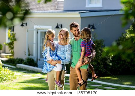 Smiling parents carrying children in yard against house