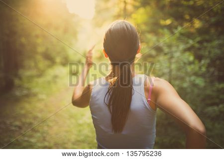 Runner woman jogging in the forest.Beautiful fit female fitness woman training and working out outside in summer as part of healthy lifestyle.Fitness woman running at sunset in woods
